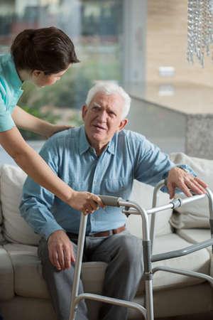Gehandicapte man met behulp van rollator en behulpzaam verpleegkundige