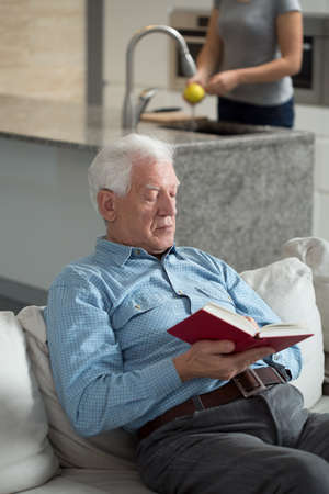 Vertical view of senior man reading book photo