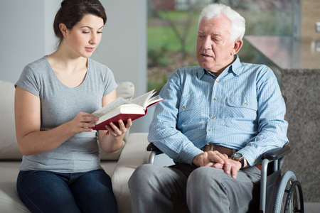 carer: Senior care assistant reading book elderly man Stock Photo