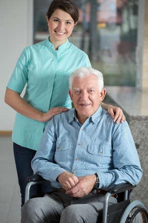 nurses: Hombre elegante usando silla de ruedas y su enfermera amablemente