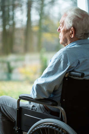 mobility nursing: Sad disabled man looking from the window Stock Photo