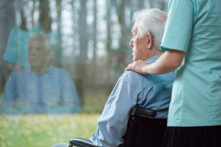 enfermeria: Cuide la ayuda de discapacidad superior al hombre usando silla de ruedas Foto de archivo