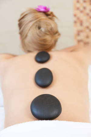 Hot stones for massage on young womans back photo
