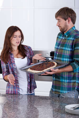 make a paste: Man holding plate with burnt homemade pizza