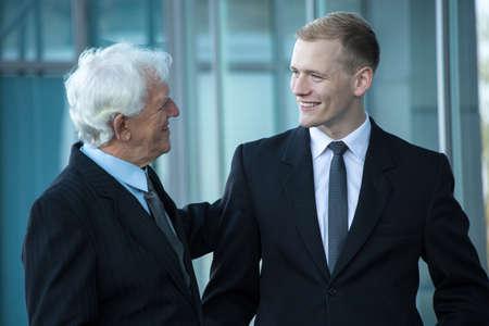 Jonge gelukkige werknemer in gesprek met zijn baas