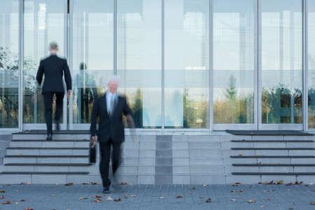 personas trabajando en oficina: Dos empleados que pasan por la puerta de la oficina