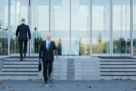 company building: Two employees passing through the offices door