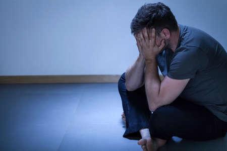 Retrato de hombre deprimido sola que se sienta en el suelo Foto de archivo