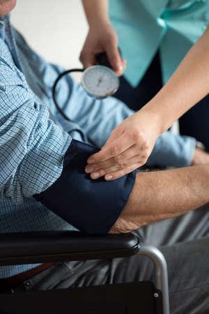 hipertension: Primer plano de hombre con discapacidad y la enfermera con esfigmoman�metro