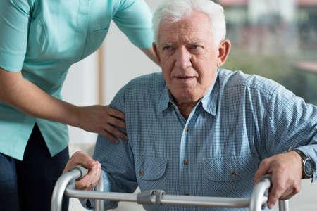 social worker: Handicapped man using walker - rehabilitation at home
