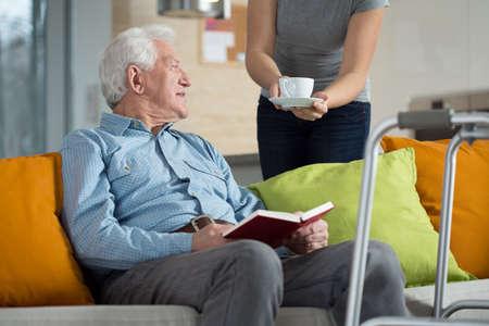 personas sentadas: Cuidador dando discapacitados hombre taza de caf�