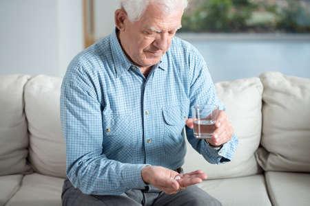 Enfermo del hombre mayor que toma la píldora y el agua potable