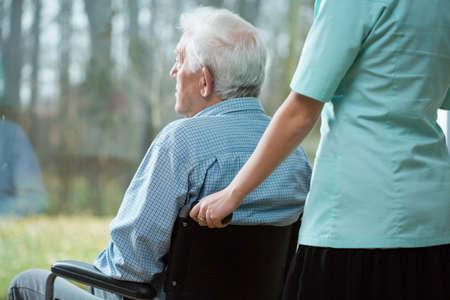 Verpleegster en gehandicapte man kijkt uit het raam