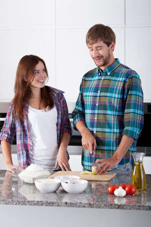 make a paste: Portrait of young couple preparing italian meal Stock Photo