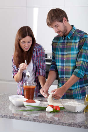 make a paste: Vertical view of couple doing pizza at home
