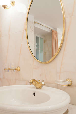 handbasin: Oval mirror with gold elements in luxury bathroom
