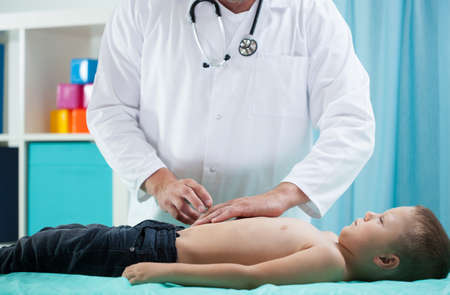 Image of pediatrician doing abdominal examination 스톡 콘텐츠