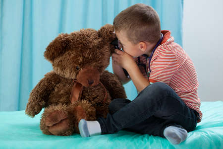 human infection: Young boy playing in doctor with bear