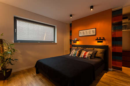 hotel bedroom: Designer bedroom with orange wall and color cushions Stock Photo