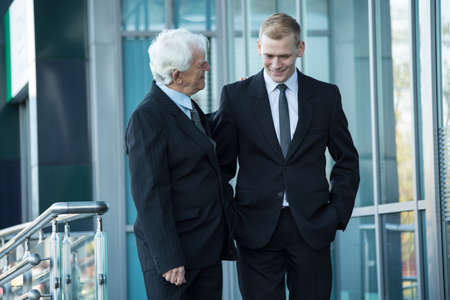company employee: Elderly boss giving the praise to his young employee