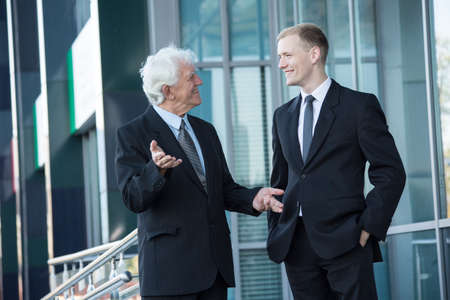 happy workers: Elderly director and young worker talking outside the building Stock Photo