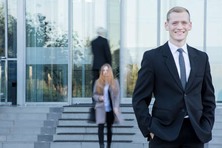 Young happy businessman waiting outside the building for a girl