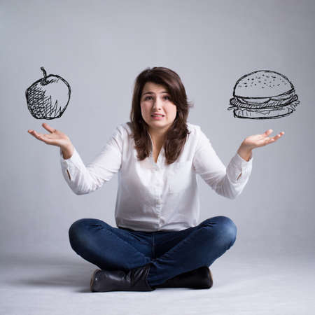 decission: Pretty girl with a dilemma about food Stock Photo