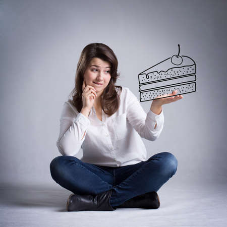 decission: Girl dreaming about eating a piece of cake Stock Photo