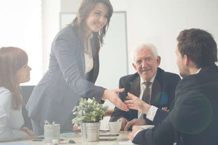 Horizontal view of businesswoman greeting with co-workers
