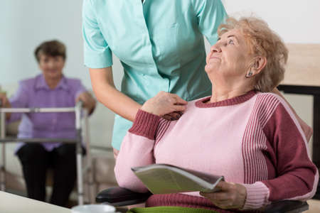 home care nurse: Young caring therpist and senior woman in nursing home Stock Photo
