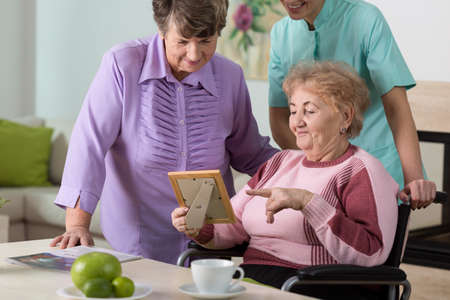 color therapist: Two aged women and young therapist looking at picture