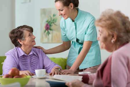 persona de la tercera edad: Joven enfermera muy cari�oso y sus dos salas Foto de archivo