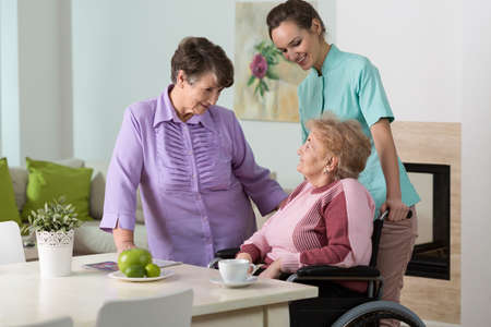 color therapist: Two aged women and young nurse spending together happy afternoon Stock Photo