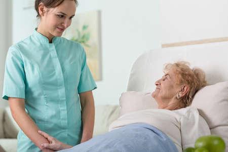 Jonge mooie verpleegster en haar oudere zieke patiënt in het ziekenhuis bed