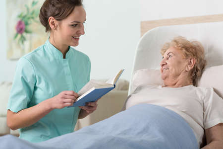 color therapist: Young beautiful nurse reading to sick older woman in bed