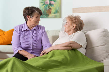 2 people at home: Older sick woman in hospital and her friends visit Stock Photo