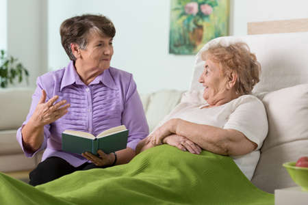병원에서 아픈 친구와 시간을 보내는 할머니 스톡 콘텐츠