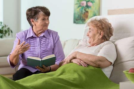 chory: Starsza kobieta spędzać czas z jej chorego przyjaciela w szpitalu Zdjęcie Seryjne