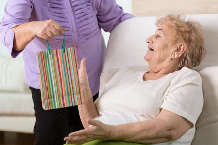 get help: Sick elderly woman getting the gift from her old good friend