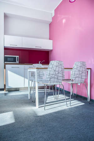 kitchenette: Dining room with kitchenette painted in pink Stock Photo