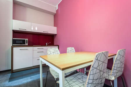 small room: Kitchen and dinning room with rose wall Stock Photo