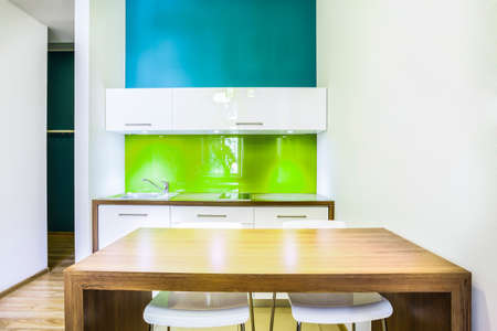 Green dining space with kitchenette in hotel room photo