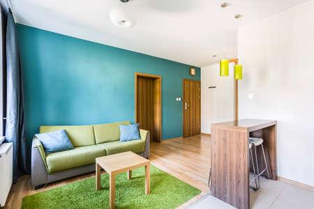 シアンの壁と緑のソファとスタジオ アパート インテリア
