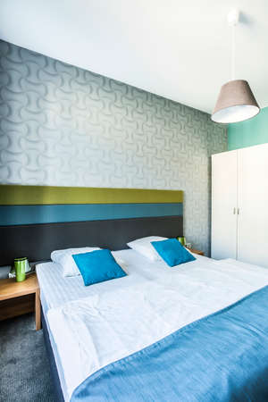 double bed: Spacious bedroom with twin bed in hotel room
