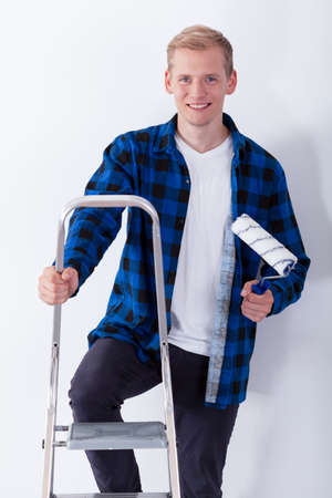 redecorating: Young man on ladder redecorating his bedroom