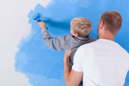 check room: Horizontal view of boy painting wall in dads arms Stock Photo