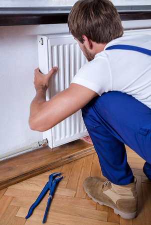 regulating: A handyman in overalls installing a white radiator in a room Stock Photo