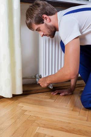regulating: A repairman fixing a radiator in a flat