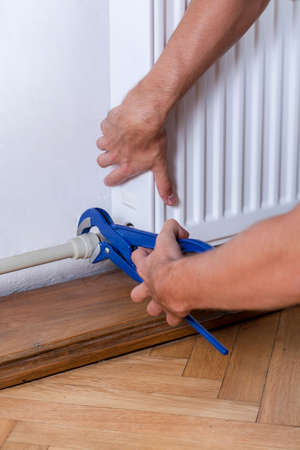 regulating: A closeup of a handyman regulating a radiator with a monkey wrench
