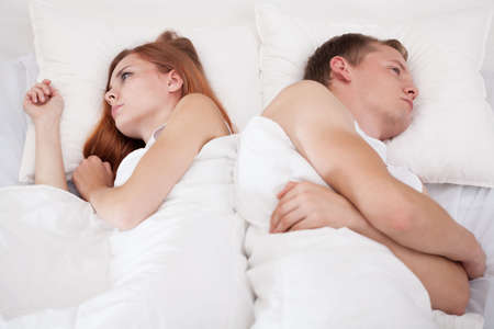 Young offended couple lying in bed after fight Stock Photo